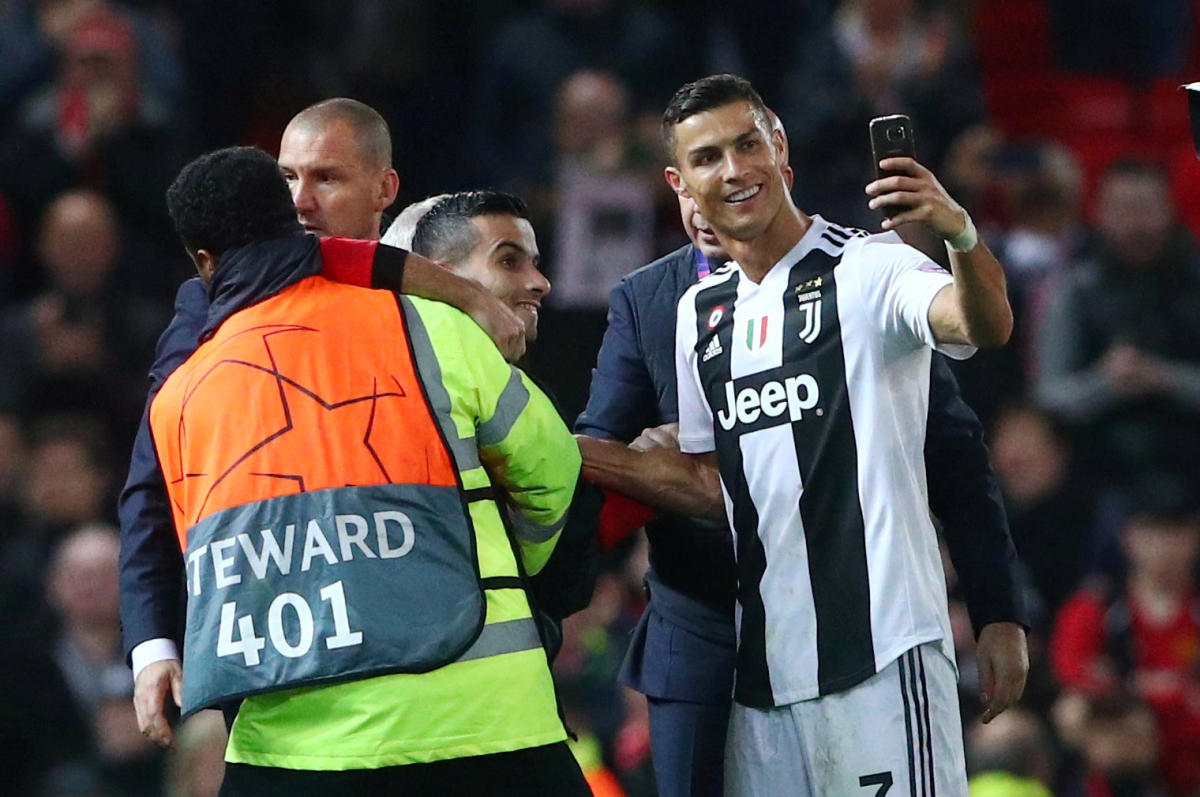 Soccer Football - Champions League - Group Stage - Group H - Manchester United v Juventus - Old Trafford, Manchester, Britain - October 23, 2018 Juventus' Cristiano Ronaldo takes a selfie as stewards apprehend a pitch invader after the match REUTERS/Hanna