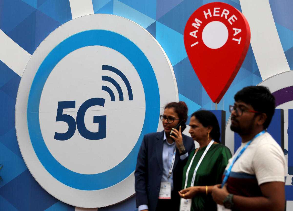 People stand in front of a board depicting 5G network at the India Mobile Congress 2018 in New Delhi on Friday. REUTERS