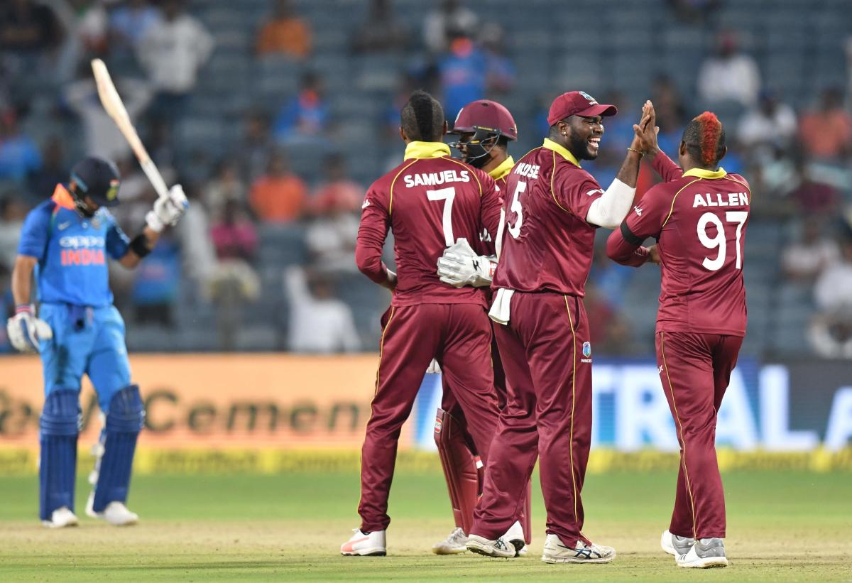 West Indies players celebrate after the wicket of India captain Virat Kohli during the third one day international (ODI) cricket match between India and West Indies at the Maharashtra Cricket Association Stadium in Pune on October 27, 2018. (Photo by PUNI