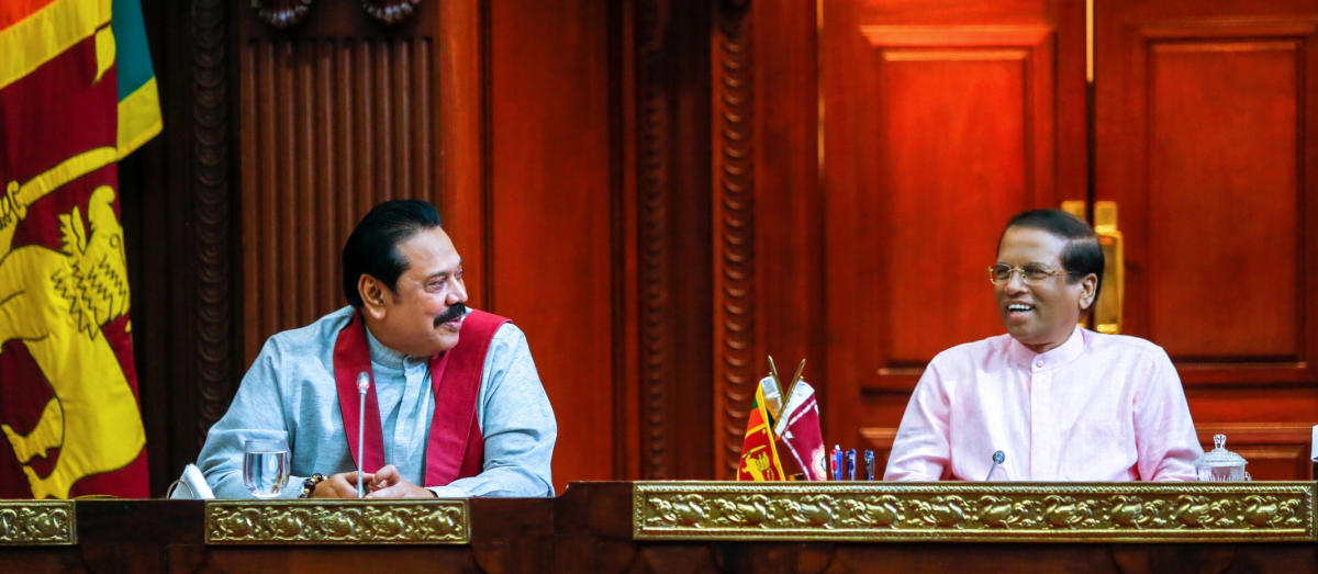 Sri Lanka's newly appointed Prime Minister Mahinda Rajapaksa (L) smiles next to President Maithripala Sirisena during their party members' meeting in Colombo, Sri Lanka October 27, 2018. Sri Lanka's President's Office/Handout via REUTERS