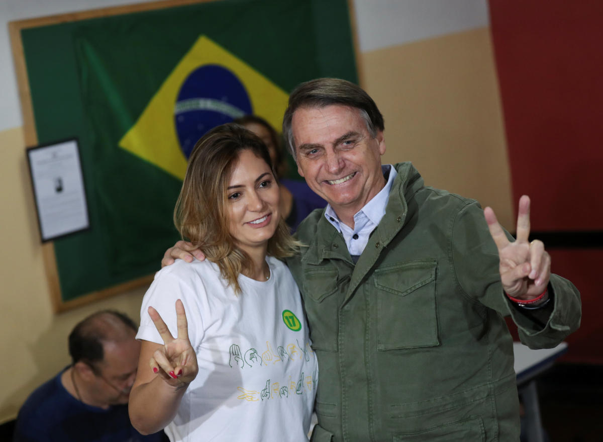 Jair Bolsonaro, far-right lawmaker and presidential candidate of the Social Liberal Party (PSL), poses with his wife Michelle as they arrive to cast their votes, at a polling centre in Rio de Janeiro, Brazil October 28, 2018. REUTERS