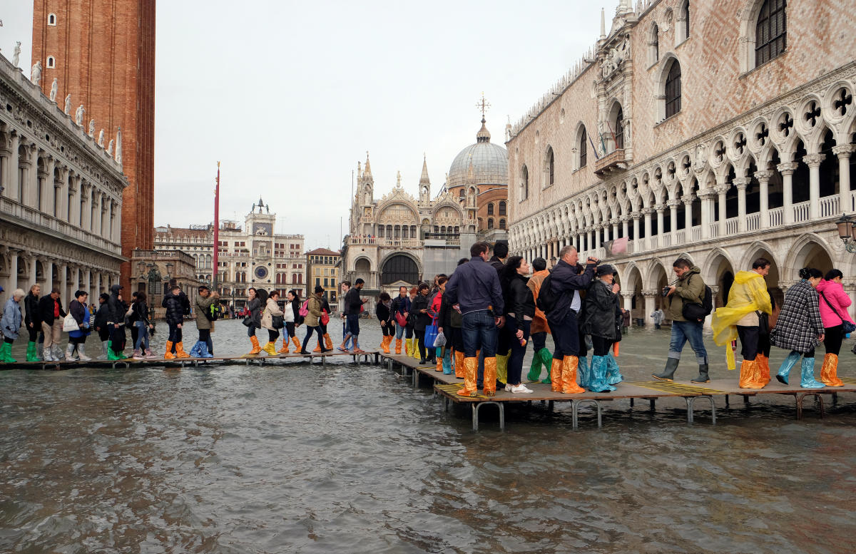 People walk on a catwalk in a flooded Saint Mark Square during a period of seasonal high water in Venice, Italy October 29, 2018. (Reuters)