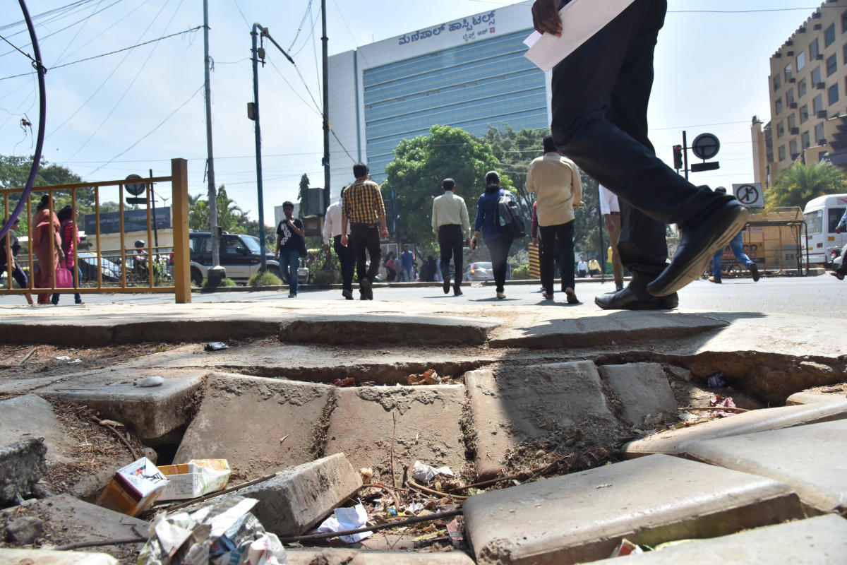 TELL-ALL: A shabby footpath just outside Manipal Hospitals on Old Airport Road. DH PHOTO/JANARDHAN B K