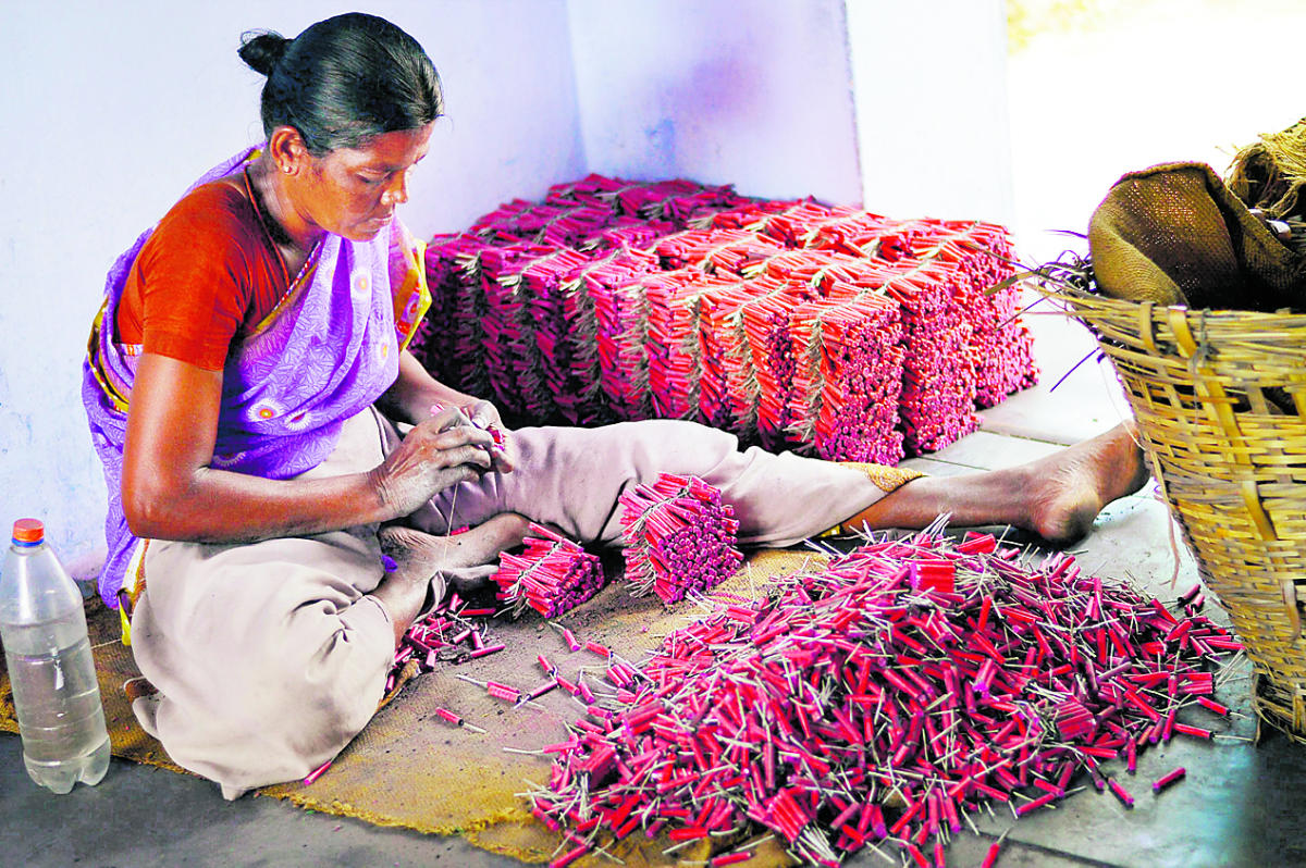 Sivakasi: A woman employee making crackers at a factory in Sivakasi district in Tamil Nadu. The firecrackers business may be hit by crores due the ban on its sale in Delhi National Capital Region till October 31. PTI Photo(PTI10_10_2017_000181B)PTI10_10_