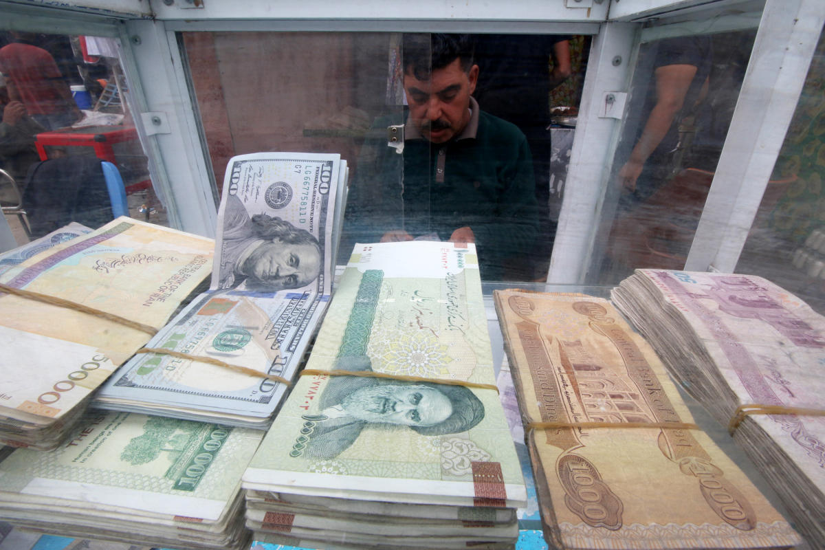 A man counts Iranian rials at a currency exchange shop, before the start of the U.S. sanctions on Tehran in Basra. Reuters photo