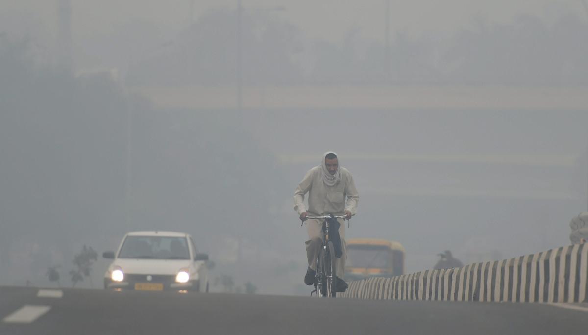 A cyclist rides through heavy haze, in New Delhi. PTI photo
