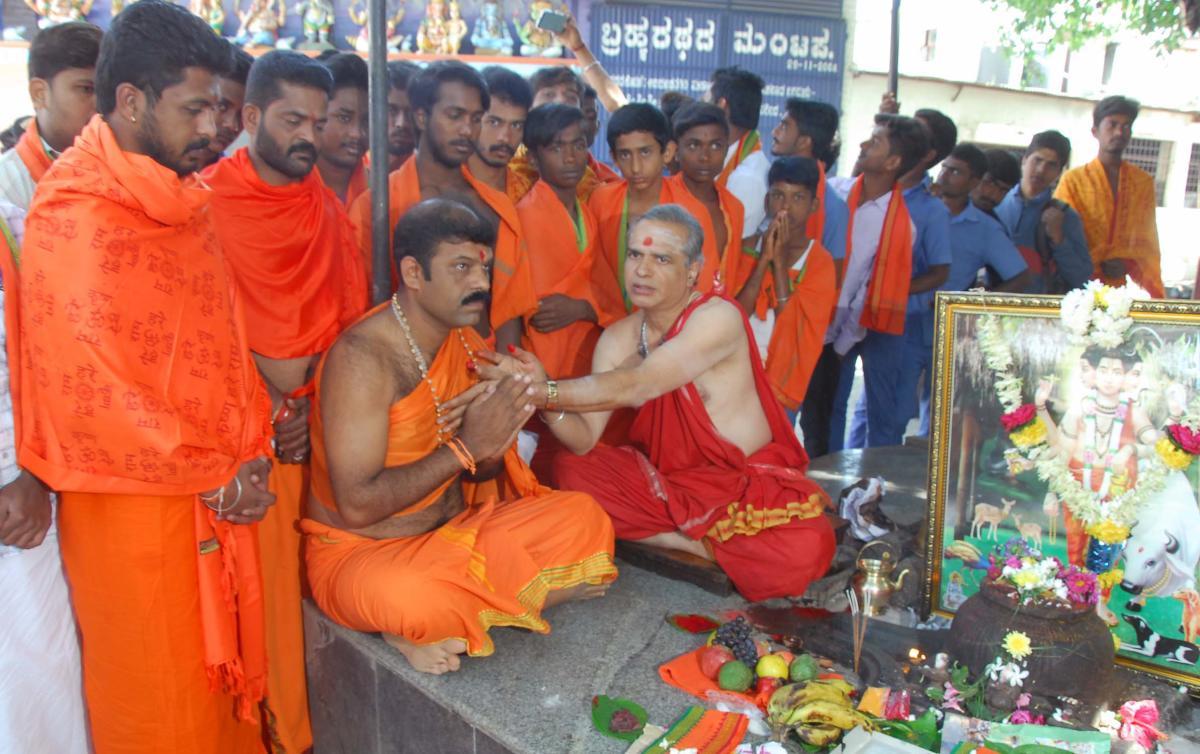 Priest Chandru offering Dattamala to Maheshkumar Kattinamane in Chikkamagaluru on Monday.