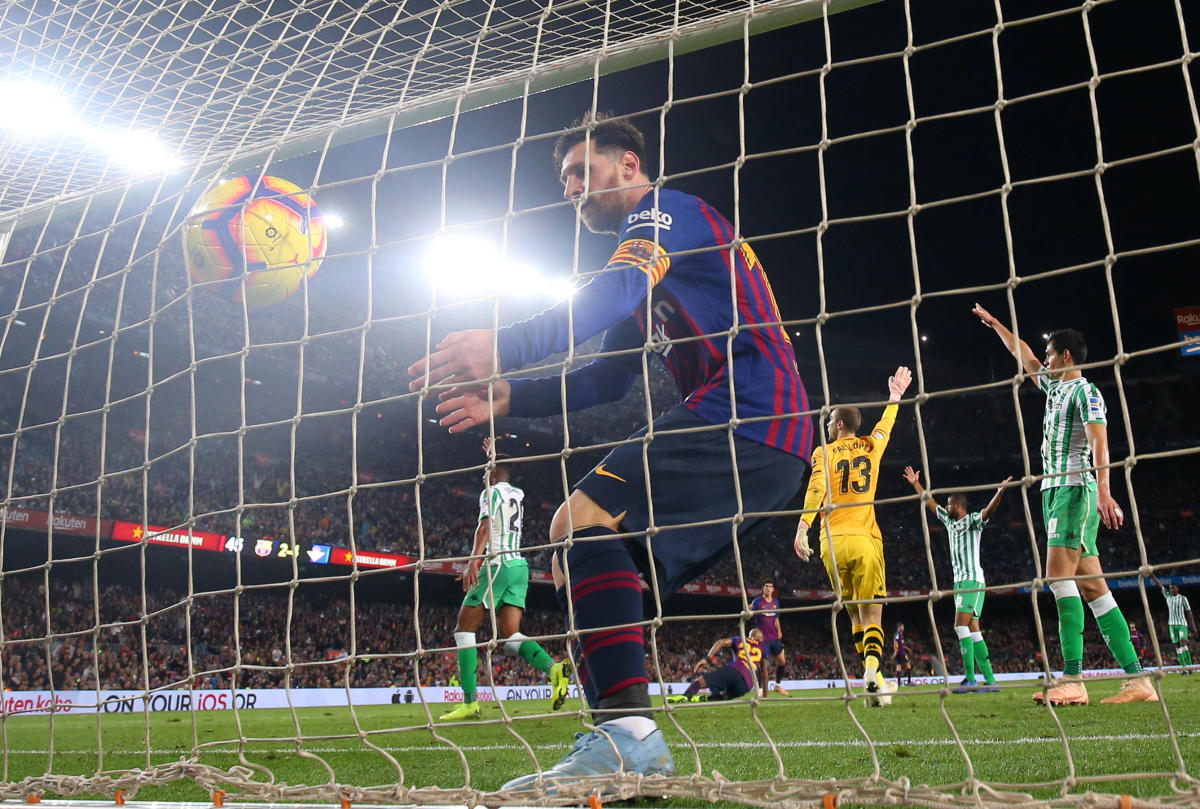 Barcelona's Lionel Messi collects the ball from the goal net after scoring their third goal against Real Betis on Sunday. (REUTERS)
