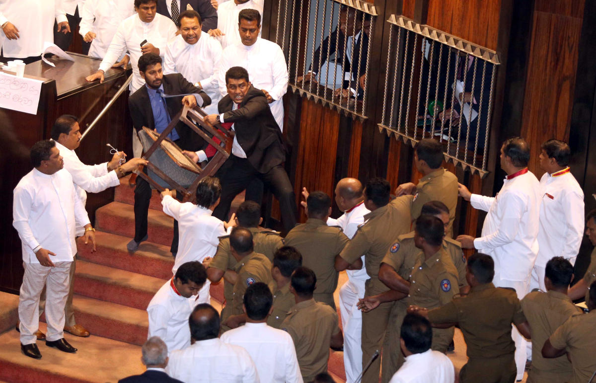 Parliament member Johnston Fernando who is backing newly appointed Prime Minister Mahinda Rajapaksa throws a chair at police who are there to protect parliament speaker Karu Jayasuriya (not pictured) during a parliament session in Colombo, Sri Lanka Novem