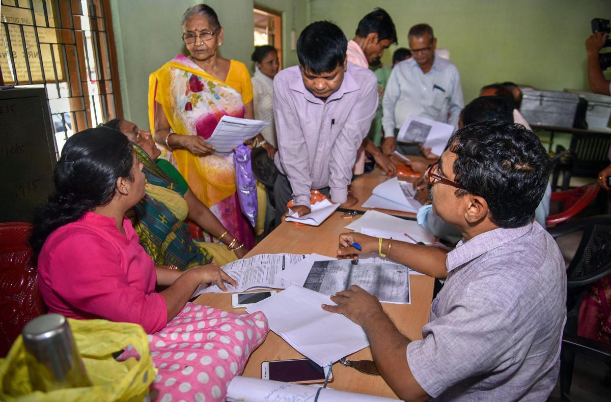 People verify the National Register of Citizens (NRC) forms to file claims and objections at an NRC centre, in Guwahati. (PTI Photo)
