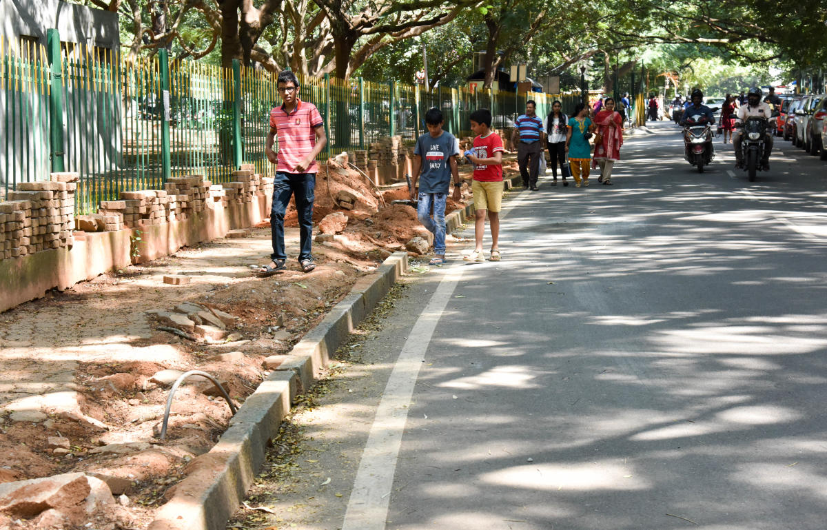 Citizens have a hard time walking on a footpath in Cubbon Park, which is under repair.