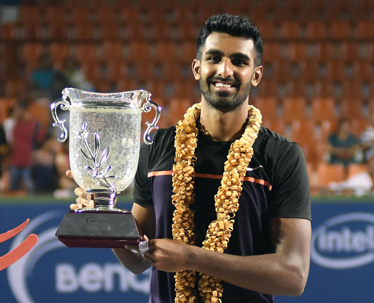 TOP GUN: Prajnesh Gunneswaran with the Bengaluru Open trophy after defeating Saketh Myneni in Bengaluru on Saturday. Prajnesh won 6-2, 6-2. DH Photo/ Srikanta Sharma R