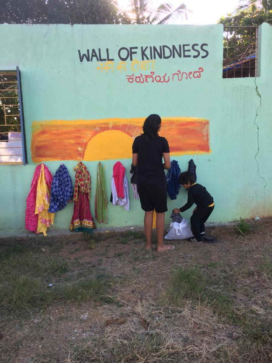 The residents of Whitefield hanging clothes at the 'Wall of Kindness'.