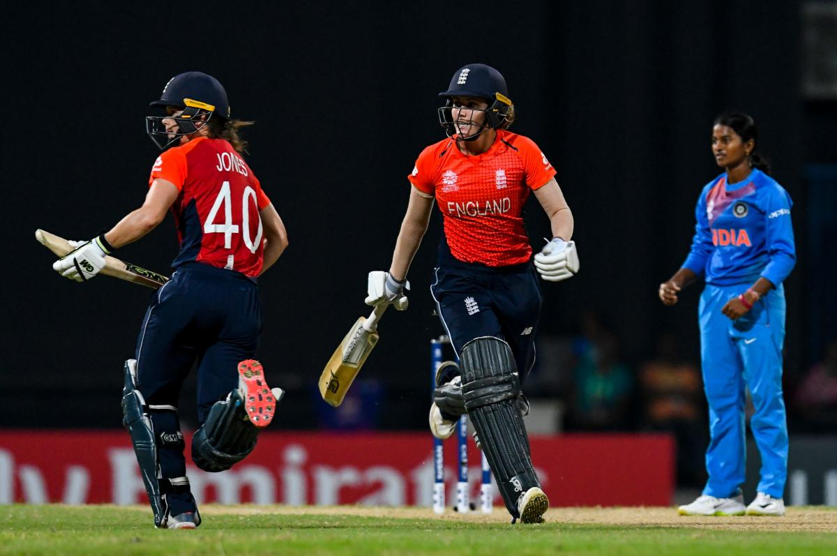 Amy Jones (L) and Nat Sciver (C) of England 50 runs partnership as Dayalan Hemalatha (R) looks on during the ICC Women's World T20 2nd semi-final match between England and India at Sir Vivian Richards Cricket Ground, North Sound, Antigua and Barbuda, on November 22, 2018. (Photo by Randy Brooks / AFP)