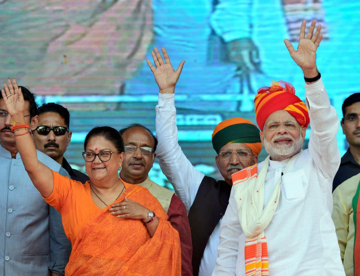 Prime Minister Narendra Modi and Rajasthan Chief Minister Vasundhara Raje greet their supporters during 'Vijay Sankalp Sabha', in Ajmer, on Saturday. PTI