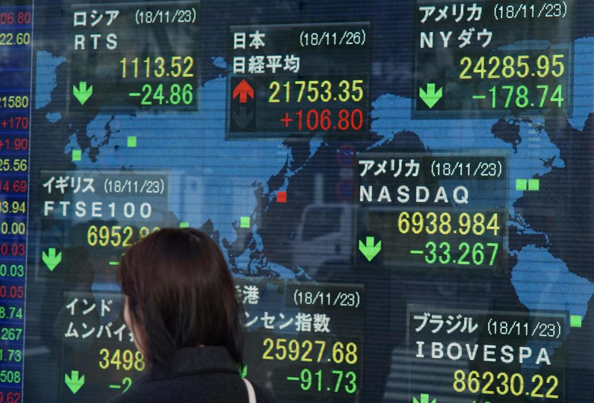 A woman walks past a stock indicator board showing the share prices of the Tokyo Stock Exchange (C, top) and other major markets in Tokyo on November 26, 2018. - Tokyo stocks opened slightly higher November 26 as investors looked beyond negative news such