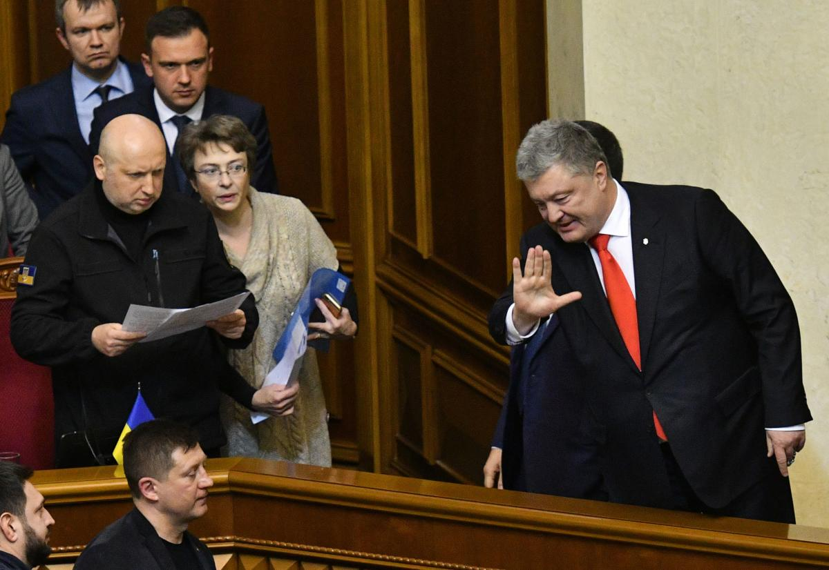 Secretary of the National Security and Defence Council of Ukraine Oleksandr Turchynov (left) watches as Ukrainian President Petro Poroshenko (right) waves to Ukrainian MPs after they voted on the request of the Ukrainian President to impose martial law in