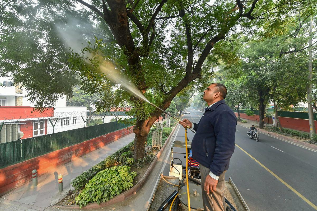 A New Delhi Municipal Council (NDMC) worker sprinkles water on trees to combat toxic smog and dust near India Gate, in New Delhi, Tuesday, Nov. 27, 2018. (PTI Photo)