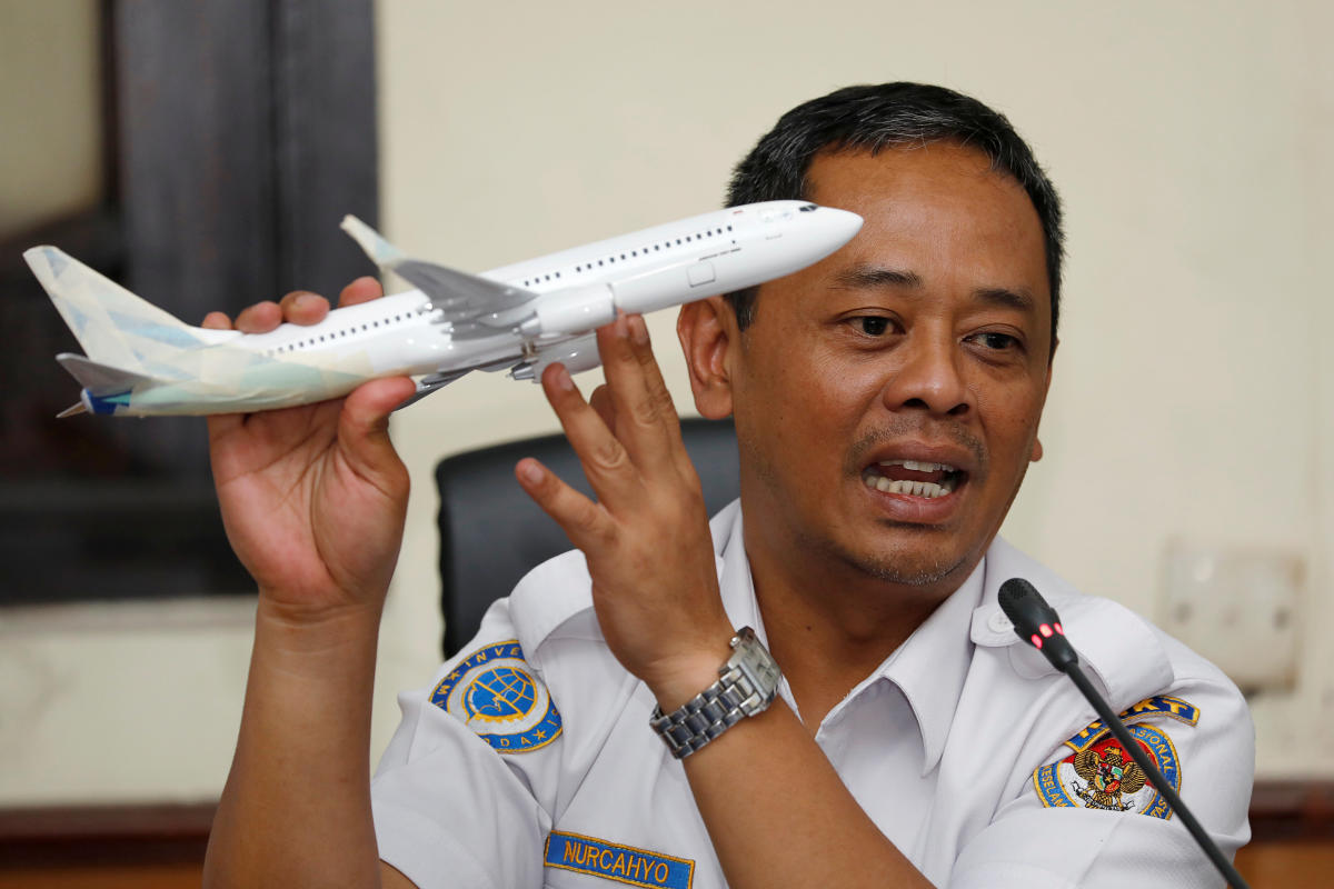 Indonesia's National Transportation Safety Committee sub-committee head for air accidents, Nurcahyo Utomo, holds a model airplane while speaking during a news conference on its investigation into a Lion Air plane crash last month, in Jakarta, Indonesia
