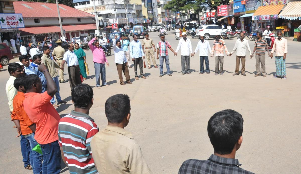 Members of Bhoomi Matthu Vasati Vanchitara Horata Samiti conduct a protest at Azad Park Circle in Chikkamagaluru on Wednesday.