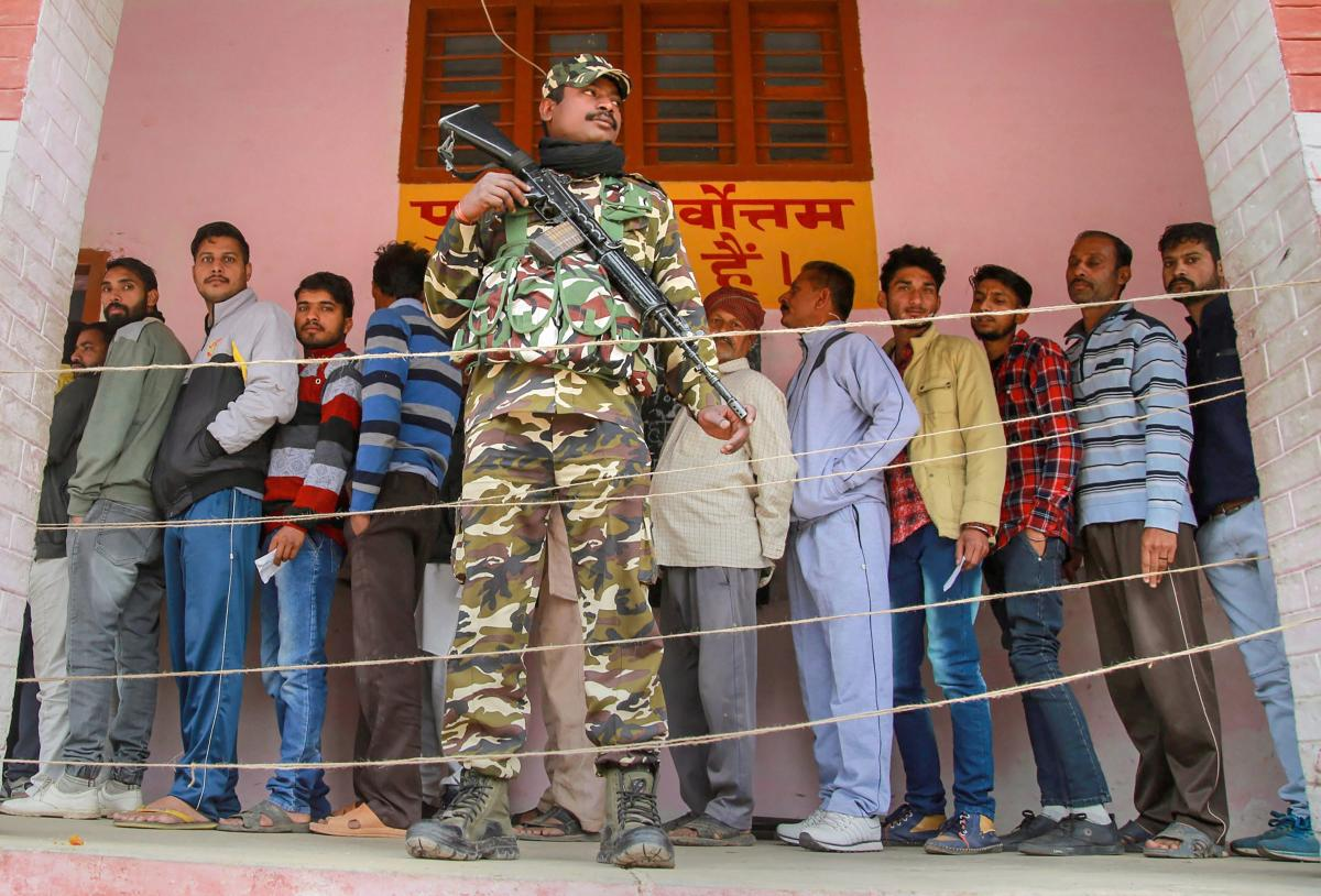 Security personnel stand guard as voters stand in a queue at a polling station during the 5th phase of the panchayat elections at Aghore village, in Jammu, Thursday. PTI Photo