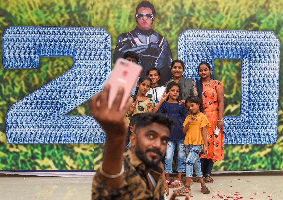 People take a selfie with the poster of Tamil actor Rajinikanth's movie '2.0' in Mumbai. PTI photo