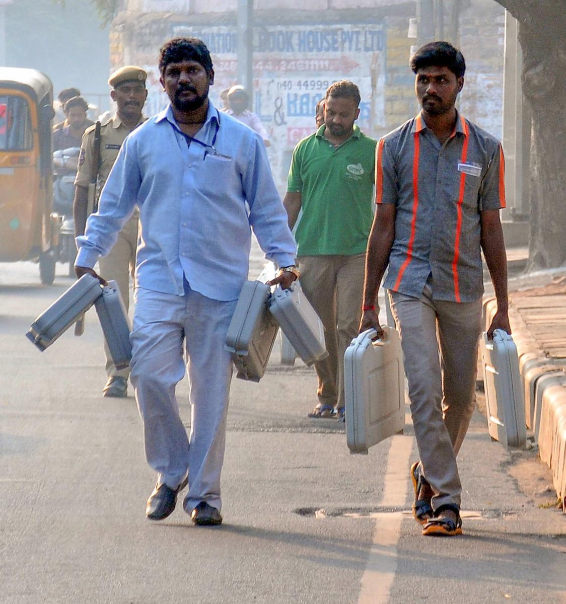 Polling officials carry EVMs to a polling station at Victory Playground, in Hyderabad, Thursday, Nov. 29, 2018. (PTI Photo)