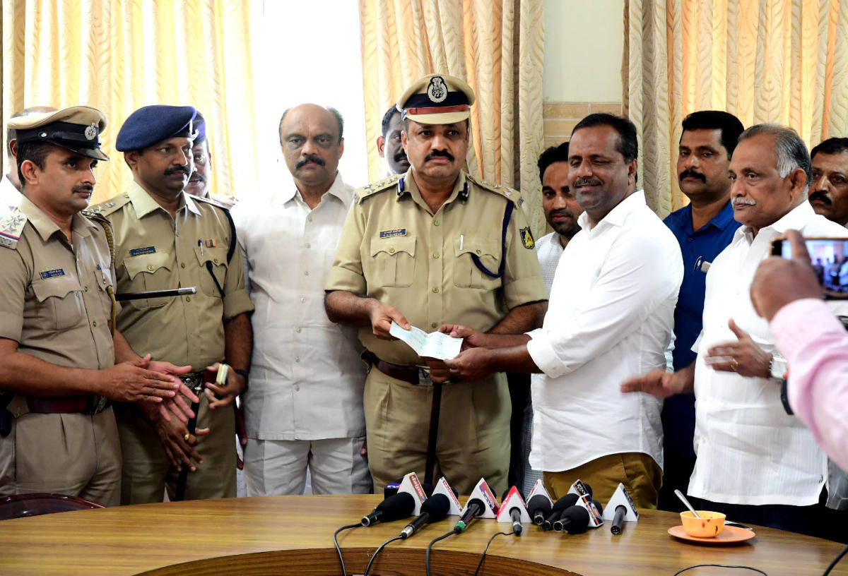 District In-charge Minister U T Khader hands over a cheque for Rs 1 lakh as a reward for Panambur police, to City Police Commissioner T R Suresh, in Mangaluru on Friday.