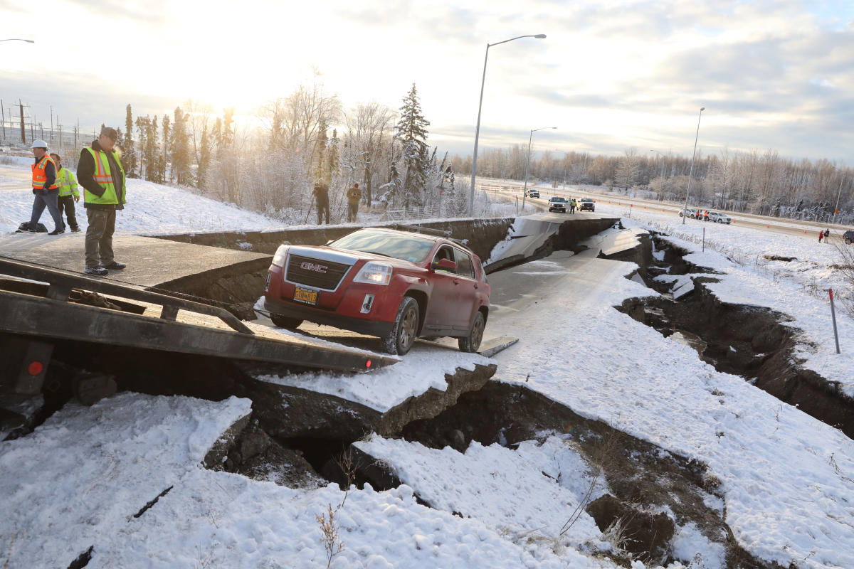 A stranded vehicle is pulled out of a collapsed section of roadway near the airport after an earthquake in Anchorage, Alaska. Reuters Photo