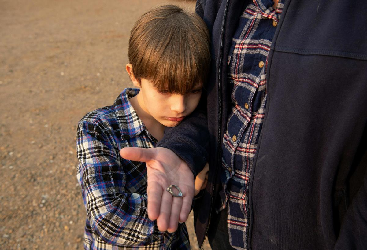 Jacob Saylors, 11, looks at the wedding ring his mother Zeatra Saylor found in the burned remains of their home in Paradise, California on November 18, 2018. - The family lost a home in the same spot to a fire 10 years prior. (AFP File Photo)