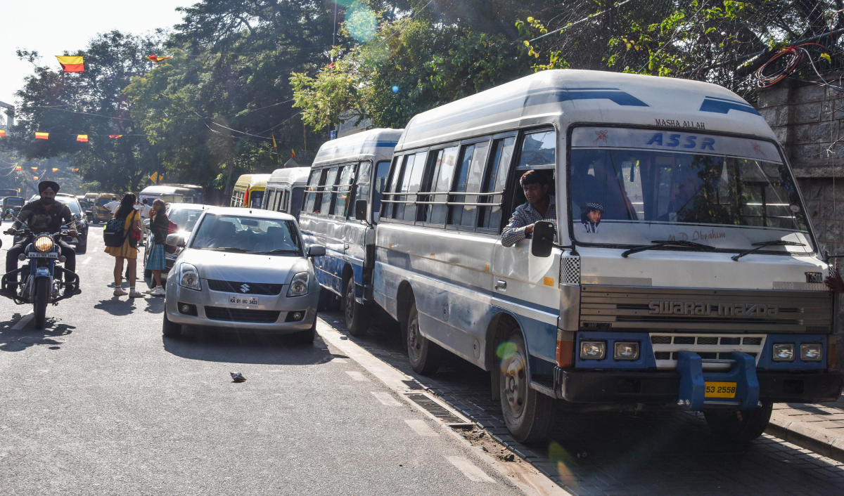 Serpentine queues: School buses, vans and other private vehicles parked haphazardly outside a school on Residency Road on Monday. DH Photo/S K Dinesh)