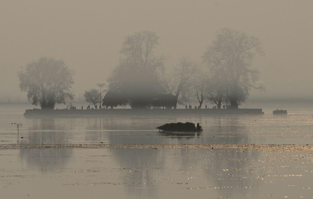 ashmiri Muslims ride a shikara boat in Dal lake amidst a dense fog in Srinagar. (AFP photo)