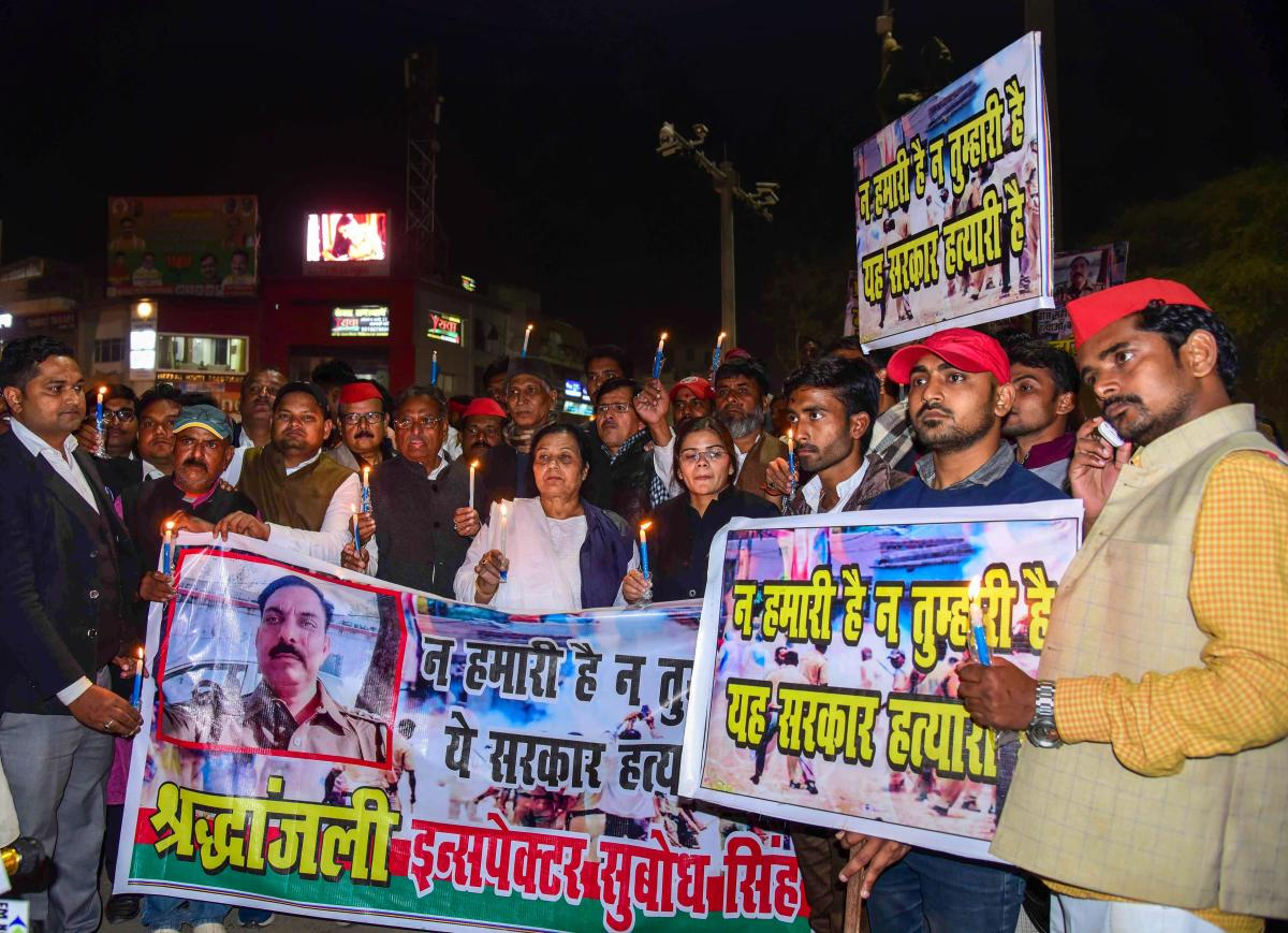 Samajwadi Party workers take part in a candlelight march to pay tribute to police inspector Subodh Singh, who was killed in Monday's mob violence in Bulandshahr, in Allahabad, on Tuesday. PTI