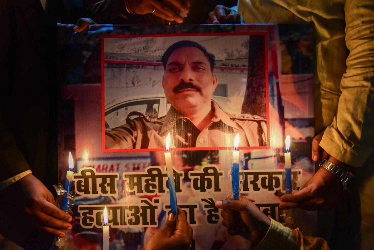Samajwadi Party workers take part in a candle light march to pay tribute to police inspector Subodh Singh, who was killed in Monday's mob violence in Bulandshahr, in Allahabad. PTI