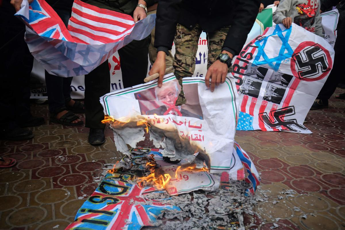 Palestinians burn makeshift flags during a demonstration against an upcoming UN General Assembly vote on a US-drafted resolution condemning the Palestinian Hamas movement in the town of Rafah in the southern Gaza Strip. AFP