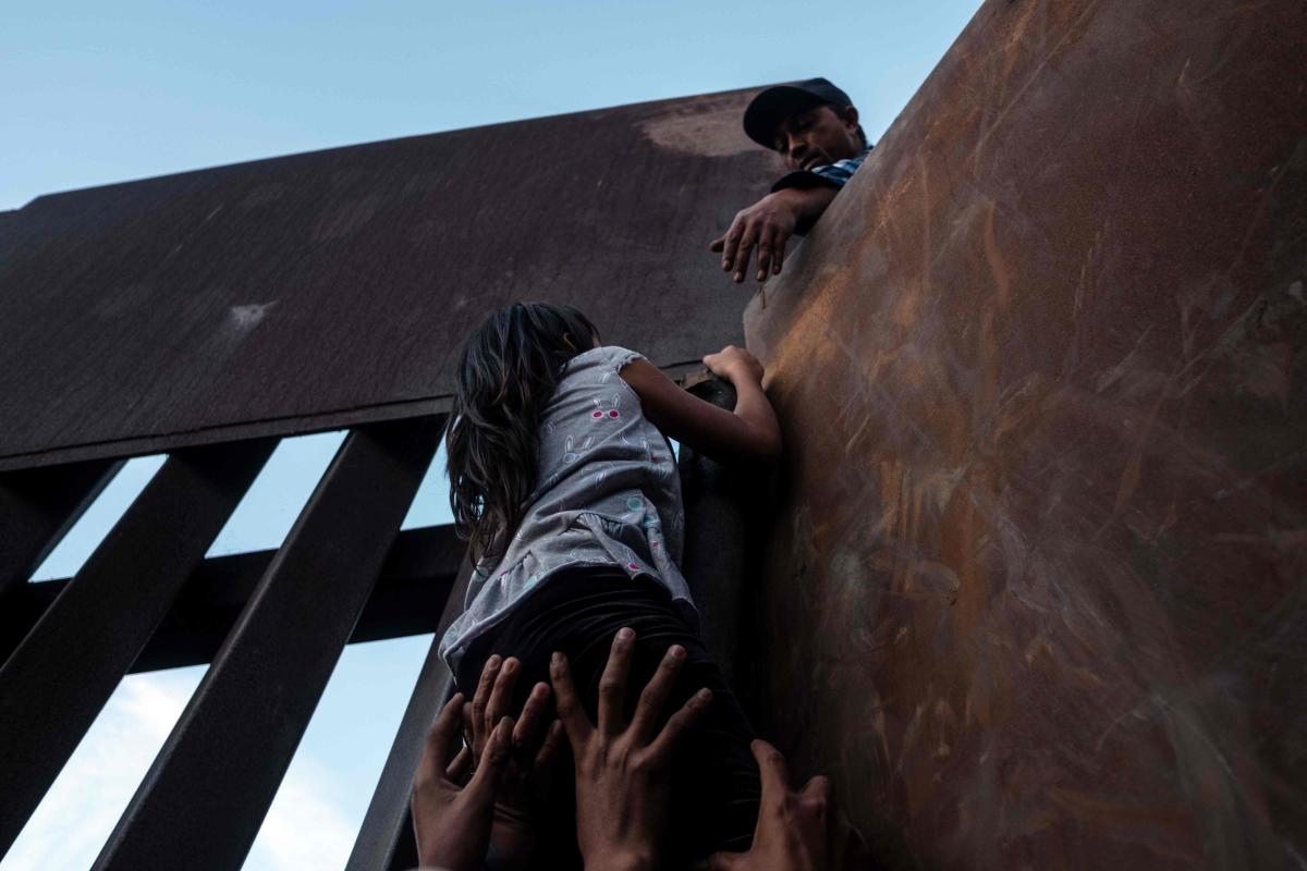 A girl who has been travelling in a caravan of Central American migrants hoping to get to the United States, is helped to climb the metal barrier separating Mexico and the US to cross from Playas de Tijuana in Mexico into the US. AFP