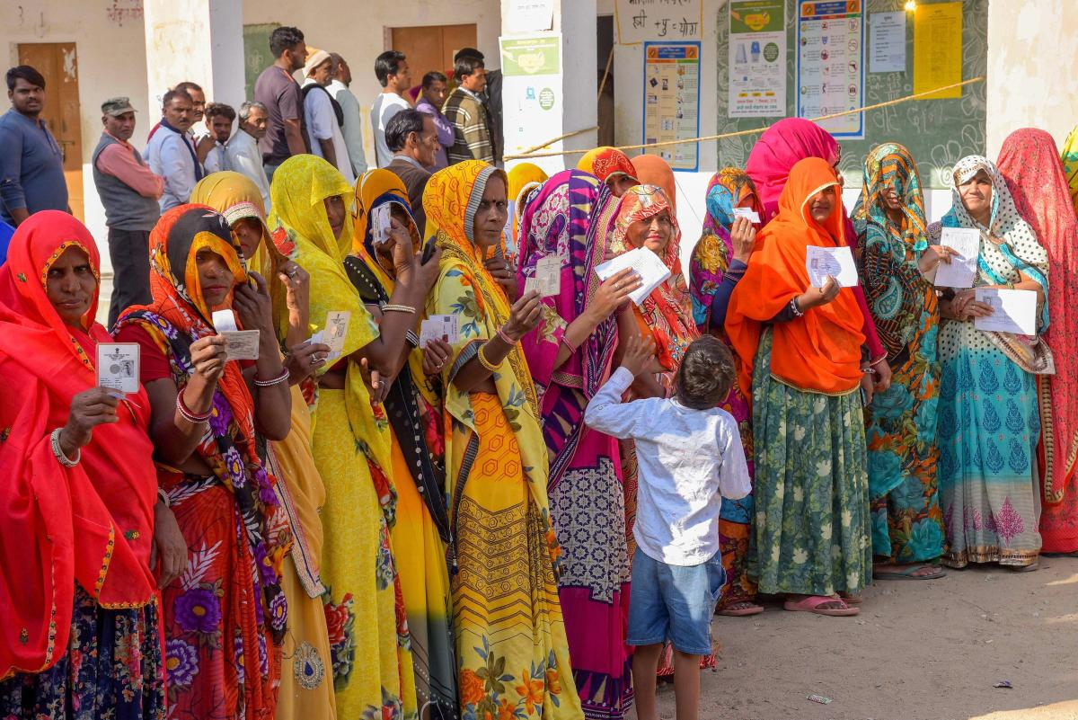 Voters show their identity cards as they wait in queues at a polling station to cast their votes for state Assembly elections, in Jaipur, Friday, Dec. 7, 2018. (PTI Photo)
