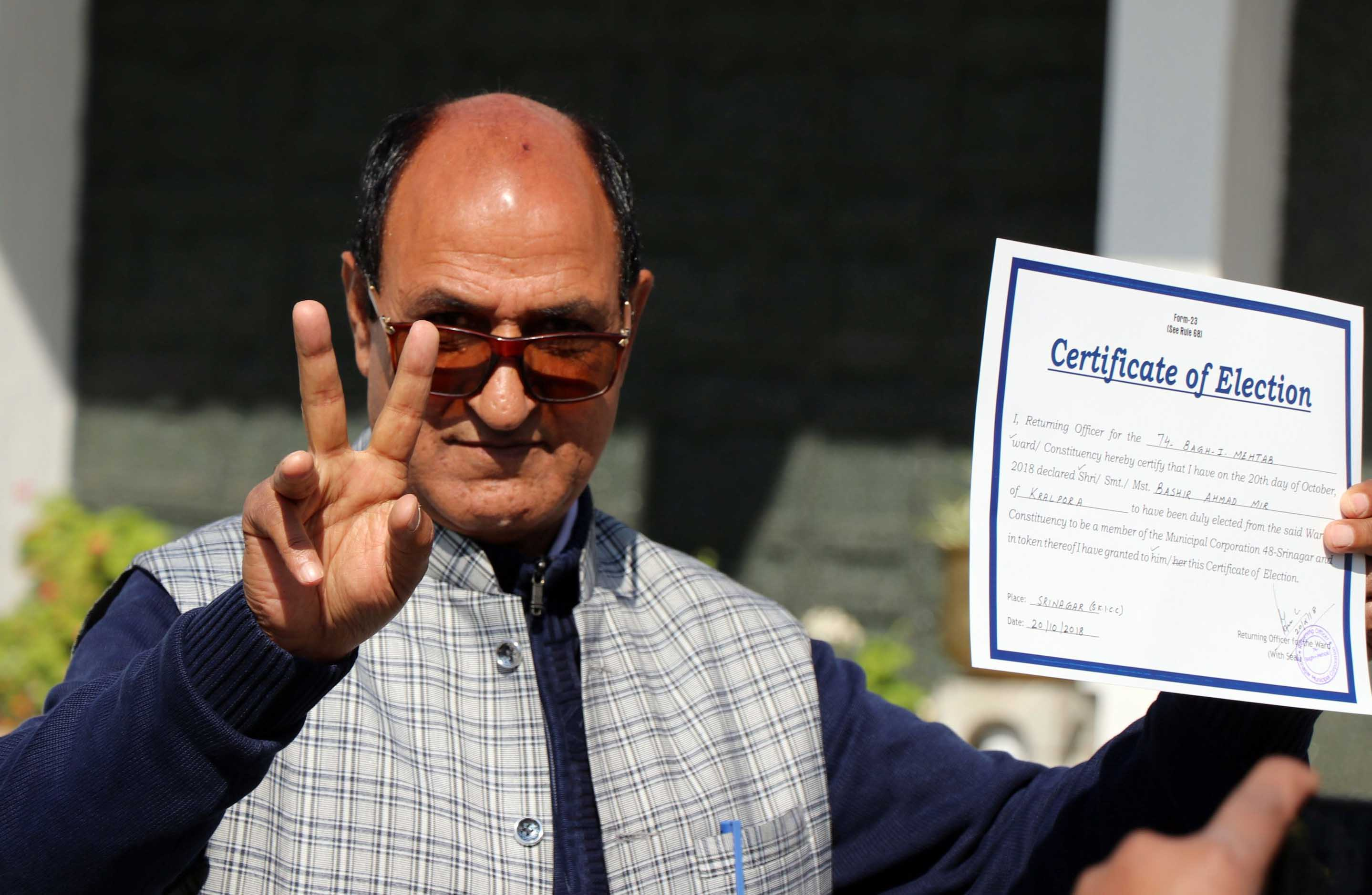 A BJP candidate shows victory sign and certificate after winning municipal election from SMC ward of Sanatnagar area of Srinagar. DH Photo