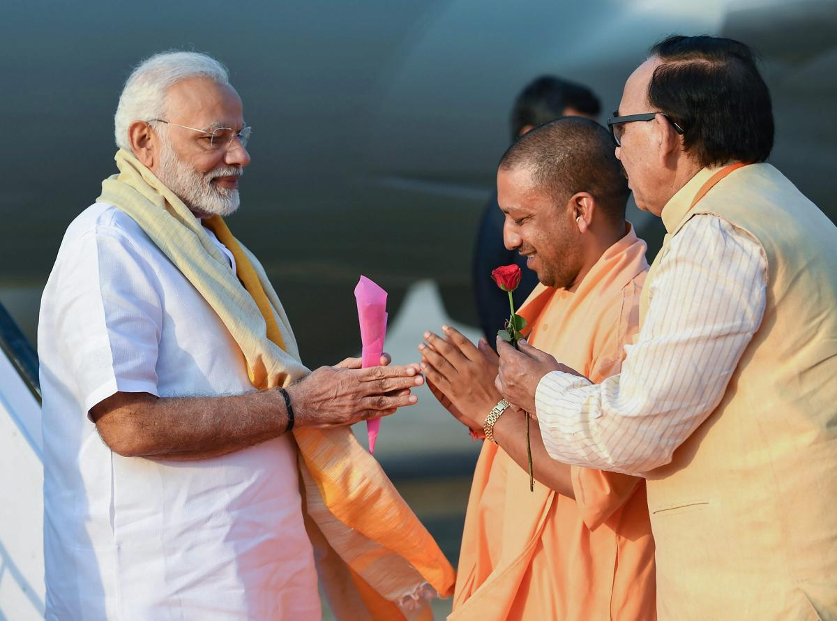 Prime Minister Narendra Modi being welcomed by the Chief Minister of Uttar Pradesh Yogi Adityanath, on his arrival in Varanasi, Uttar Pradesh, September 17, 2018. (PIB Photo via PTI)