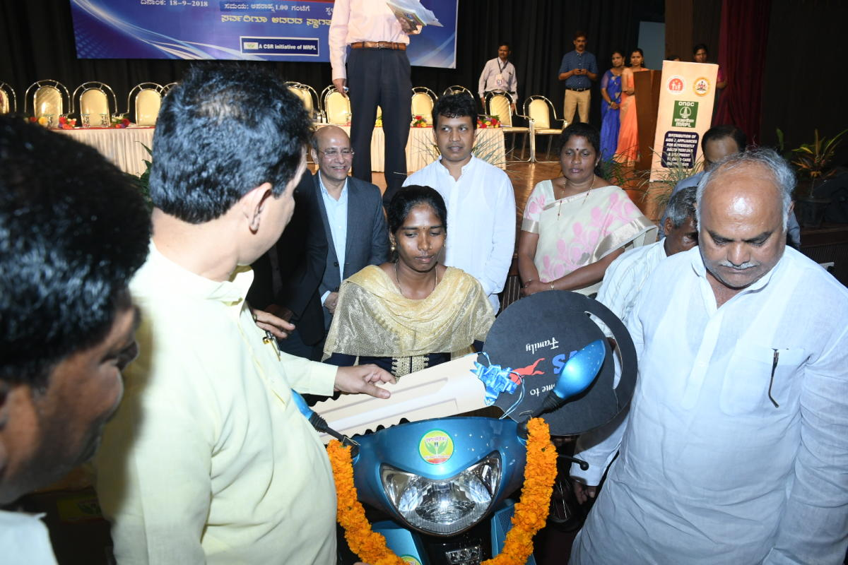 Minister for Health and Family Welfare Shivanand S Patil and MP Nalin Kumar Kateel hand over the keys of a petrol-driven two-wheeler with retro-fit kit to a beneficiary at a programme in Mangaluru on Tuesday.