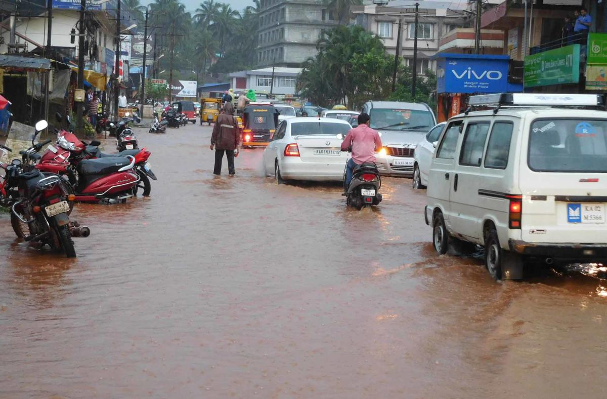 Vehicles navigate on a waterlogged road in Sirsi, Uttara Kannada district on Friday. DH Photo