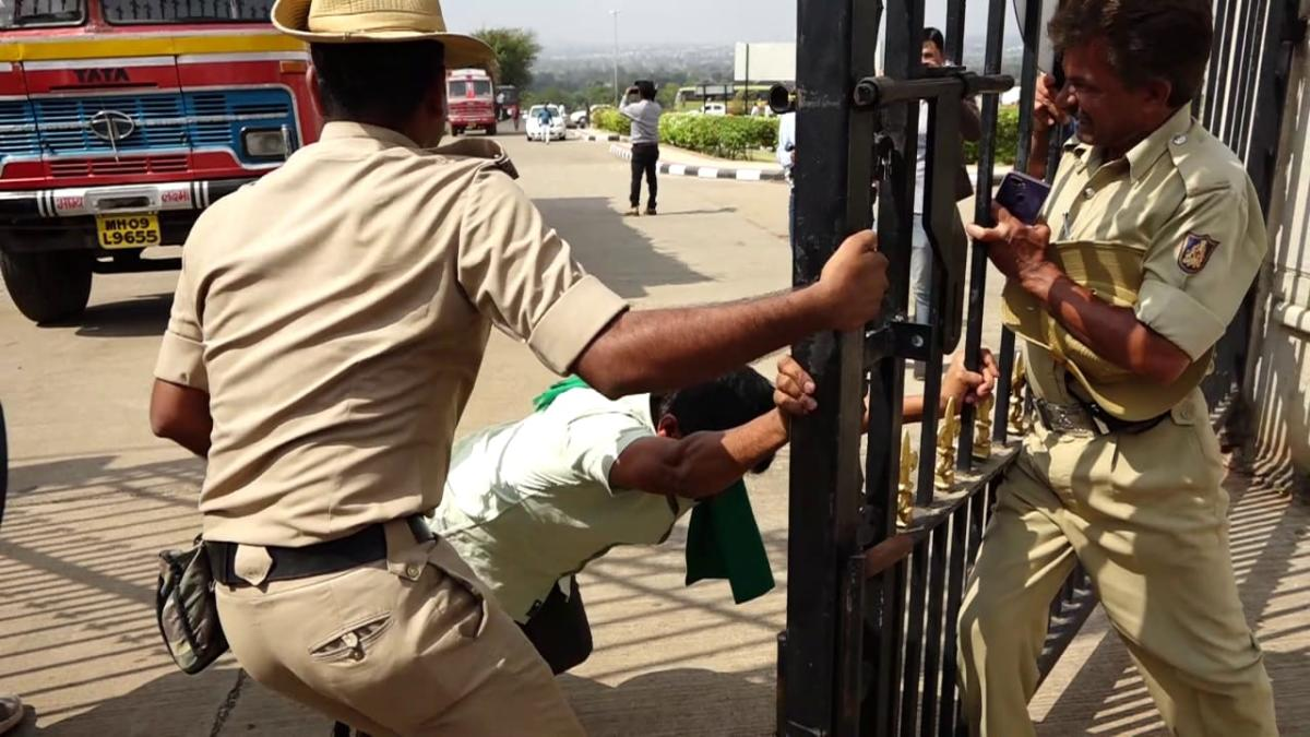 A sugarcane farmers tries to break the police cordon in Belagavi, on Sunday. DH photo.