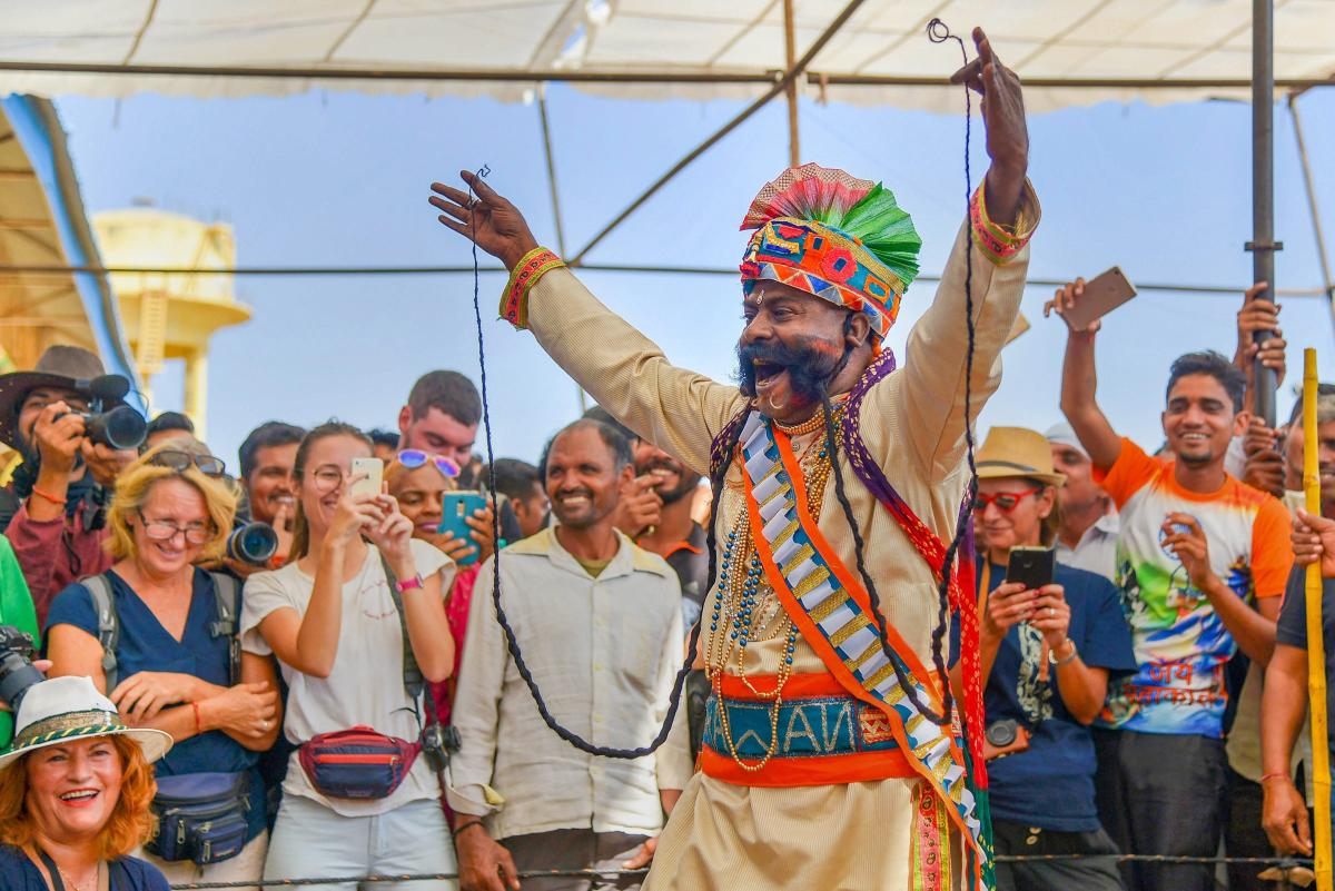 A local artist entertains tourists with his moustache at Pushkar Camel Fair, in Pushkar, Rajasthan on Tuesday. PTI