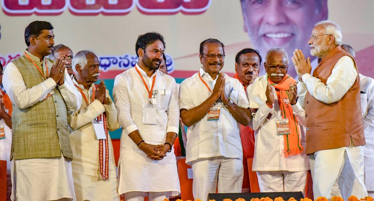 Prime Minister Narendra Modi greets his party leaders during a BJP election campaign ahead of the state Assembly elections at LB Stadium, in Hyderabad. PTI