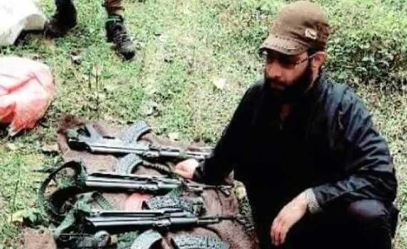 Jammu & Kashmir Special Police Officer Adil Bashir poses with the cache of arms he stole from the residence of a PDP MLA recently. (Pic courtesy Facebook)