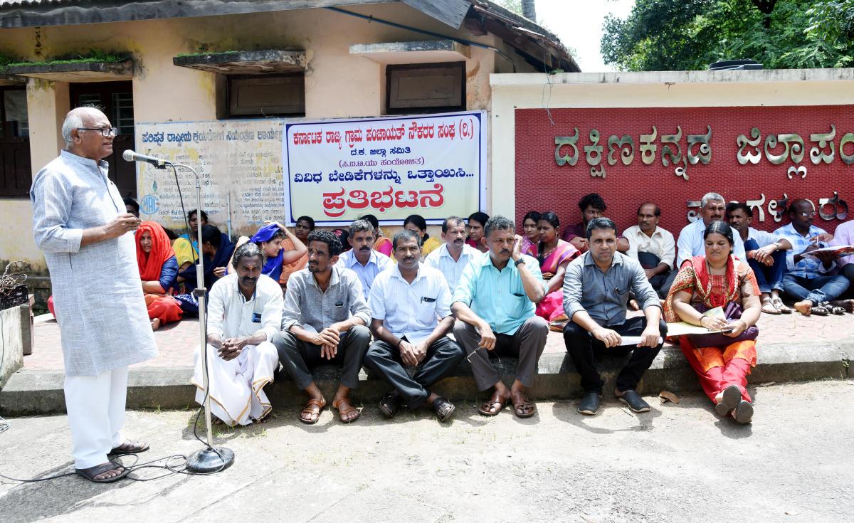 Maruthi Manpade, state president of the Karnataka Rajya Grama Panchayat Naukarara Sangha, addresses protesters in front of the Zilla Panchayat office in Mangaluru on Monday.