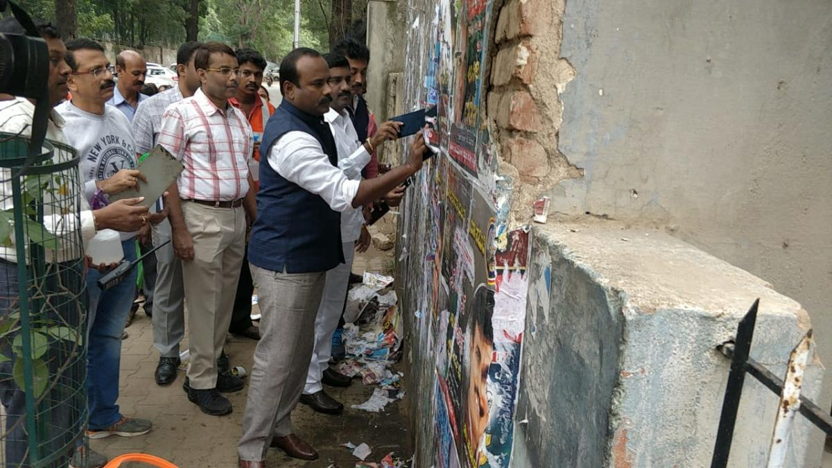 As part of an awareness campaign, Mayor R Sampath Raj, ruling party leader M Shivaraju and other BBMP officials remove posters near Palace Road on Saturday.