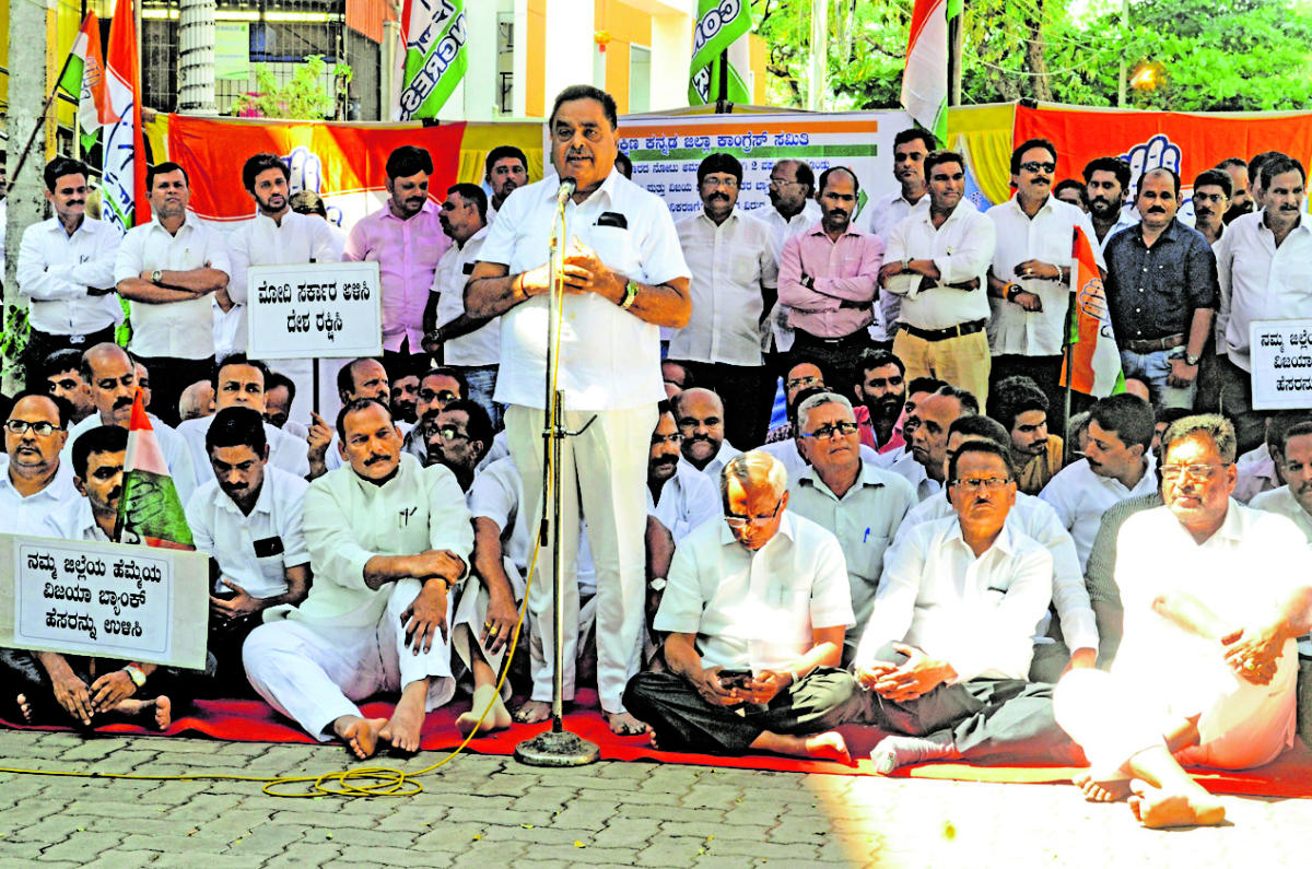 Former minister B Ramanath Rai addresses the protest organised by the District Congress Committee, to mark the second anniversary of demonetisation and proposed merger of Vijaya Bank, in front of the DCC office in Mallikatte in Mangaluru on Friday.
