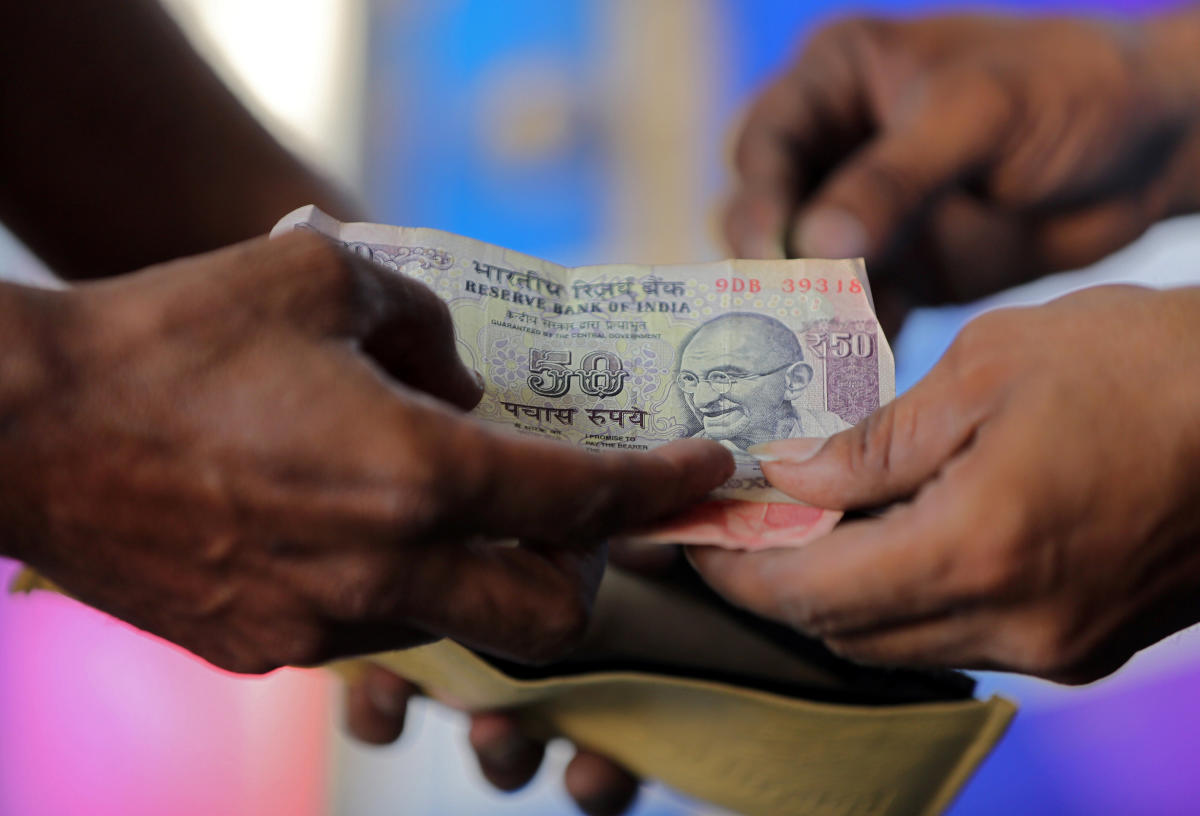 A customer hands a 50-Indian rupee note to an attendant at a fuel station in Ahmedabad. REUTERS