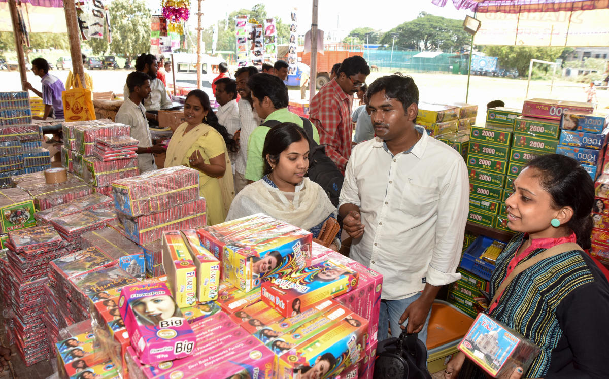 People purchase firecrackers at a shop in J K Grounds, in Mysuru, on Monday.